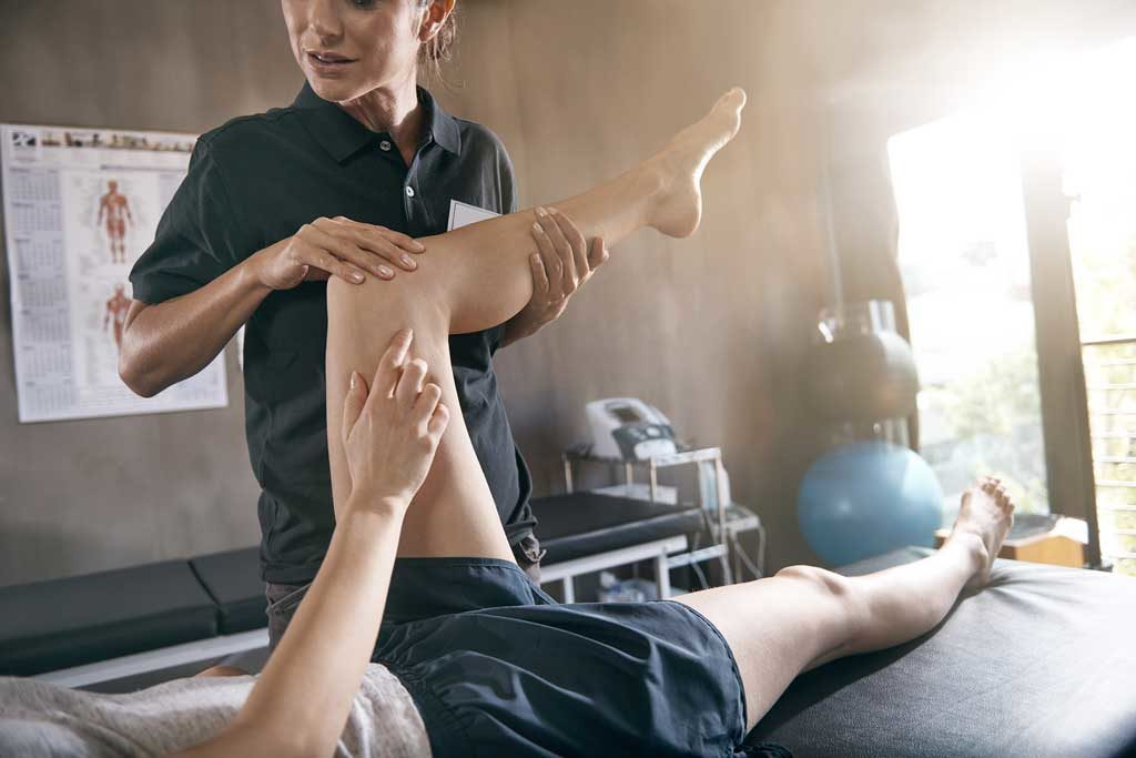 Physio treating patient's lower limb